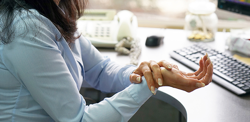 Woman at work in pain from carpal tunnel syndrome | Krasno Krasno & Onwudinjo